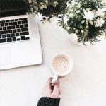 Hand holding coffee cup next to laptop and flowers