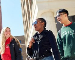 Three smiling students on Bay Campus