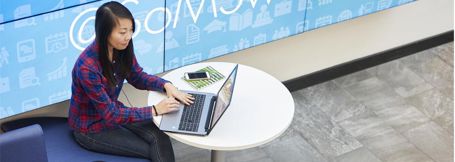 Student working on a laptop in in School of Management foyer