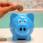 Piggy bank with a hand putting a coin in