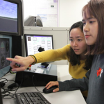Female students looking at computer