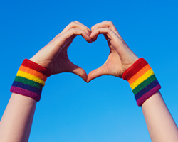 Hands with rainbow wristbands making heart shape against blue sky