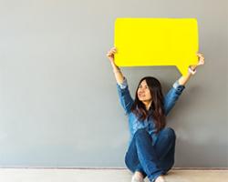 Female holding up yellow speech bubble