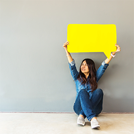 Female holding up yellow speech bubble sign. She is sitting on the floor with her legs crossed