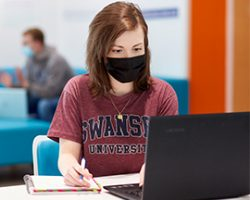 Female student working at laptop in mask