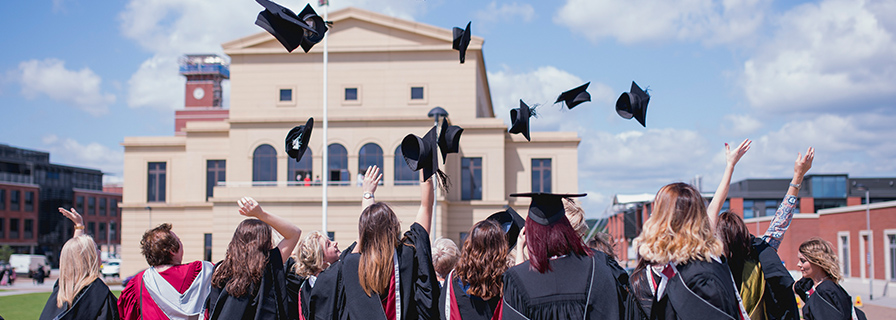 Graduates throwing their caps in the air in front of the Great Hall, Swansea University