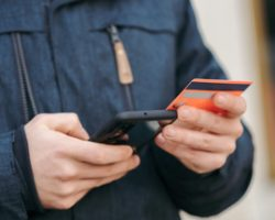Person holding a mobile phone and a credit card